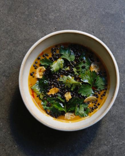 Vydatná, krémová polévka z pomalu pečené kořenové zeleniny s kokosovým mlékem, divokým kořením, černou čočkou a bylinkami