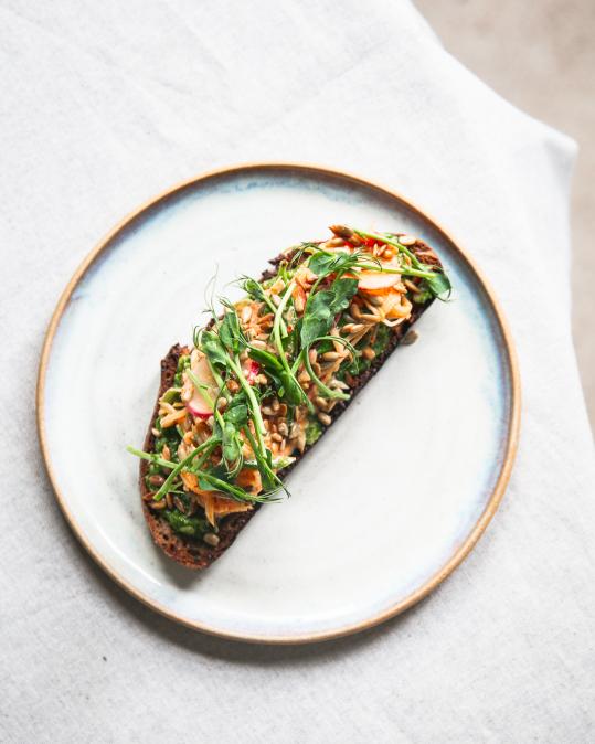 Kvásková topinka s naším pestem z medvědího česneku, salát z ředkviček a hrášku, zakyska, chilli ocet, opražená slunečnice